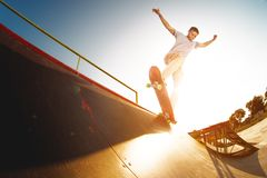 Teen skater hang up over a ramp on a skateboard in a skate park Stock Photos
