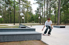Teen Skater at the Park. A teen skateboarder attempts a trick at a suburban skate park stock photos