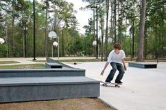 Teen Skater at the Park. A teen skateboarder attempts a trick at a suburban skate park Stock Photos