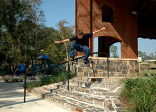 Teen Skater Stairs. A teen skateboarder executes a flying jump over a set of stairs at a suburban park stock photos