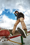 Teen skater in sweatshirt and jeans drops off the railing after sliding on a skateboard in a skate park. Wide angle Royalty Free Stock Photography