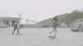 Teen skaters learning to do tricks rolling skates. Stubborn teenage friends practicing doing kickturns, rolling off drop, shuvit tricks skateboarding on sidewalk stock video footage