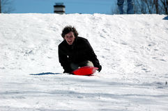 Teen sledding. A teenage boy sledding down a snow covered hill Royalty Free Stock Images