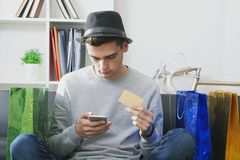 Teen with smartphone and shopping bags. Teen holding smartphone and credit card sitting surrounded by shopping bags as metaphor for online shopping Stock Photography