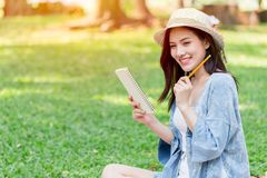 Teen smile to write note script letter. Asian teen smile to write note script letter at the park royalty free stock images