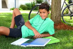 Teen smiling boy studying book garden headphones. Grass tree sitting Stock Images