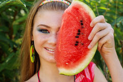 Teen smiling girl is eating watermelon on the Royalty Free Stock Photography