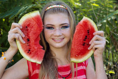 Teen smiling girl is eating watermelon on the Stock Images