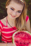 Teen smiling girl is eating watermelon on the Royalty Free Stock Photo
