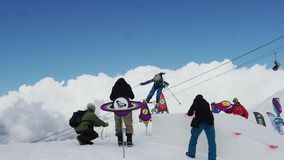 Teen snowboarder jump from springboard. Cardboard cosmic objects. Audience stock video footage