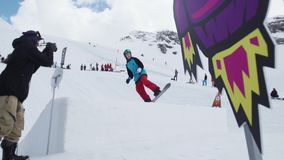 Teen snowboarder make flip from springboard. Cardboard cosmic objects. Cameraman stock video