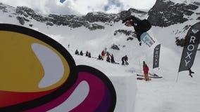 Teen snowboarder ride on springboard, make stunt. Cardboard cosmic objects. stock video footage