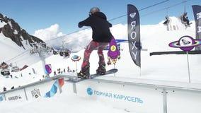 Teen snowboarder slide on trail, fail. Cardboard cosmic objects. People. Sunny stock footage
