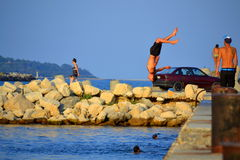 Teen somersault from pier. Teens having fun somersault from pier in blue sea water, Black sea coast, Varna, Bulgaria Stock Photography