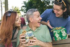 Teen son and daughter surprise dad by giving a present. Fathers. Teen son and daughter surprise dad by giving a special present. Fathers Day. Concept of family stock image