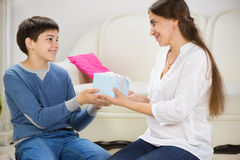 Teen son presenting a gift to mother Royalty Free Stock Photography
