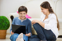 Teen son with young mother with laptop Royalty Free Stock Photo