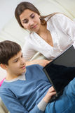 Teen son with young mother with laptop Royalty Free Stock Photos