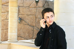 Teen speaking by phone. At the column Stock Images