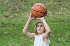 Teen sportsman. Portrait of teen sportsman with long hair catching a basketball Royalty Free Stock Image