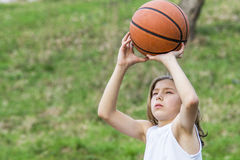 Teen sportsman. Portrait of teen sportsman with long hair catching a basketball Royalty Free Stock Photo
