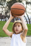 Teen sportsman. Portrait of teen sportsman with long hair catching a basketball Stock Photo