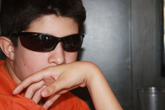 Teen Spy. Adorable young boy with sunglasses. He is pretending that he is a secret agent or spy Royalty Free Stock Photos