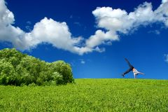 Teen stand on arm. Somersault on grass on the blue sky background Stock Images