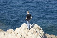 Teen standing on cliffs Stock Photos