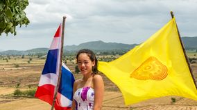 Teen standing between flags on windy day stock image