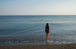 Teen standing at water`s edge with towel looking out to sea. Teen standing at water`s edge wrapped in a towel looking out to sea royalty free stock images