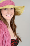 Teen with straw hat and pink scarf. On grey background royalty free stock image