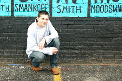 Teen on Street. Teen or young man kneels in front of grungy black brick wall Stock Photography