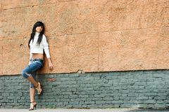 Teen in the street. Sad and Pretty Girl standing alone near grunge wall royalty free stock photography