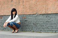 Teen in the street. Sad and Pretty Girl standing alone near grunge wall Royalty Free Stock Photos