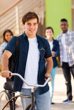 Teen student bicycle. Handsome young male teen high school student with a bicycle and friends on background Stock Photography