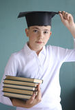 Teen student boy in graduation cap with books pile. Close up photo on blue Stock Photos