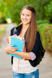 Teen student girl with books and a backpack in hands Stock Photos