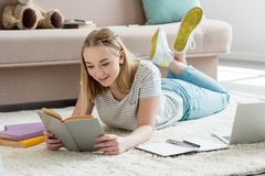 Teen student girl reading book while lying. On floor royalty free stock photo