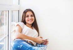 Teen student girl with smartphone at home Stock Photography