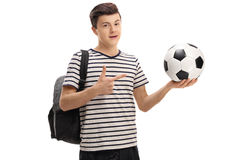 Teen student holding a football and pointing. Isolated on white background Royalty Free Stock Photo