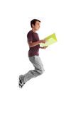 Teen student jumping. A casual dressed teenage student mid jump.  He is holding a folder and smiling.  Some motion in shoes Royalty Free Stock Photo