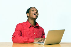 Teen Student Laughing-Horiz. Male teen student laughs as he works on his laptop computer. Horizontally framed photograph Royalty Free Stock Photo