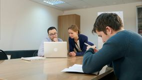 Teen student and male teacher are working on a laptop in their school lesson. Professional shot in 4K resolution. 075. You can use it e.g. in your commercial Royalty Free Stock Photography