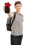 Teen student showing phone wrapped with red ribbon as present. Teen student showing a phone wrapped with red ribbon as a present isolated on white background Royalty Free Stock Image