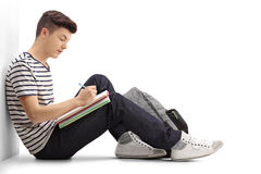 Teen student writing in a notebook. And leaning against a wall isolated on white background Stock Photos