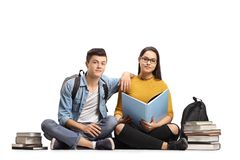 Teen students with books sitting on the floor. And looking at the camera isolated on white background Stock Photo
