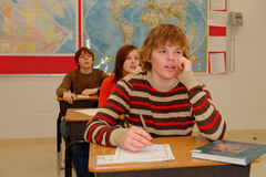 Teen Students Learning. Three Students in Classroom listen to lesson Royalty Free Stock Photo