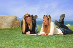 Teen Students Studying. Two pretty teen girls laying on a grassy park area studying a book Royalty Free Stock Images