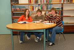 Teen Study Group. Three teens working together as they review books in the library Royalty Free Stock Images